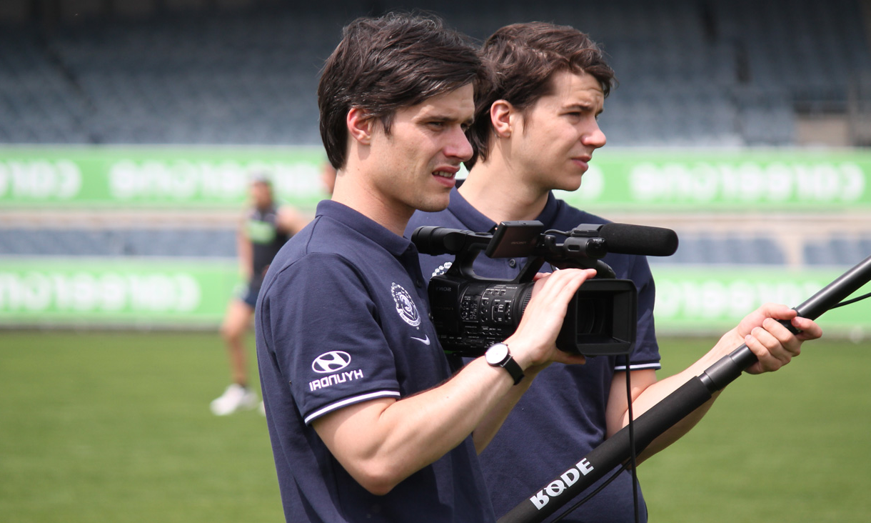 Darcy holding a video camera on a football field